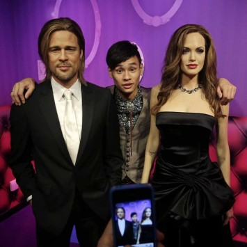 A man poses for photographs between wax figures of actor Brad Pitt and actress Angelina Jolie during a preview visit at a Madame Tussauds Museum in Wuhan