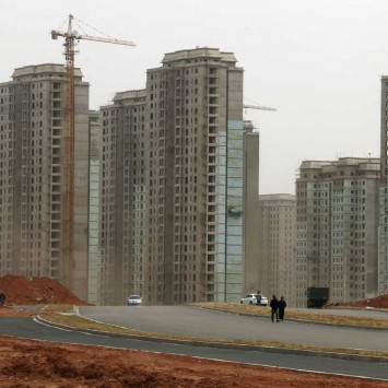 People walk along a new street surrounded by residential buildings under construction in the Kangbashi district of the town of Ordos in China's Inner Mongolia Autonomous Region