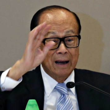 Hutchison Whampoa Chairman Li Ka-shing reacts beside a bottle of Watsons distilled water during a news conference in Hong Kong