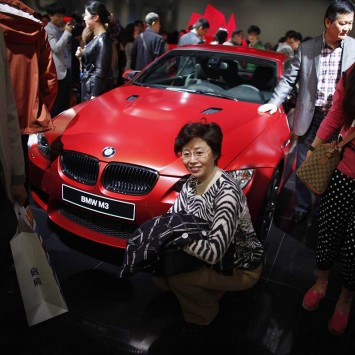 A woman poses for a picture next to a BMW M3 car during the 15th Shanghai International Automobile Industry Exhibition in Shanghai
