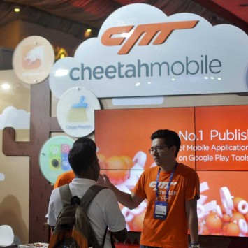 """A visitor listens to a briefing by employees of China's Cheetah Mobile at the company's information kiosk at """"Surge 2016"""" in Bengaluru"""