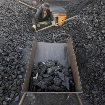 A villager selects coal at a local businessman Sun Meng's small coal depot near a coal mine on the outskirts of Jixi in China
