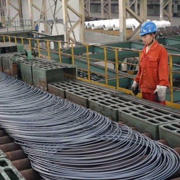 A labourer looks at steel coils next to a production line of Dongbei Special Steel Group Co., Ltd., in Dalian