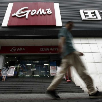 Man walks past a GOME store in Shanghai