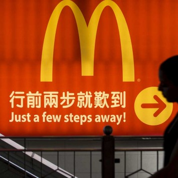 File photo of a woman walking past a McDonald's outlet in Hong Kong