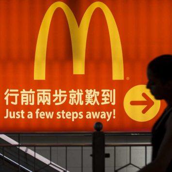 A woman walks past a logo of McDonald's in Hong Kong